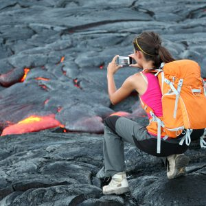 Student on tour in Hawaii photographing lava on a volcano