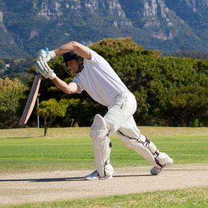 Cricket player batting among mountainous scenery