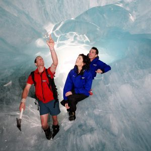 Guide with two clients inside an ice cave on Franz Josef Glacier