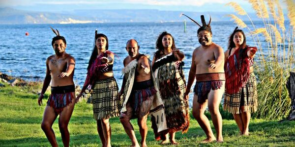 Māori cultural group performs in traditional dress at the shores of Lake Taupō