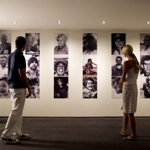 Man and woman observing a photographic exhibition at the National Museum of Australia