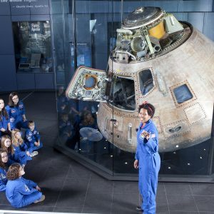 Space camp instructor speaks to students in front of the Apollo 16 capsule
