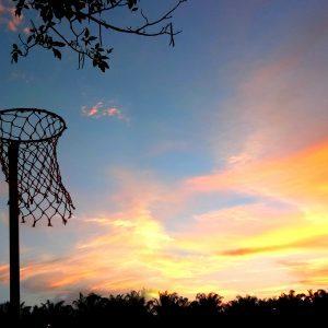 An outdoor netball hoop silhouette set against the sky at dusk