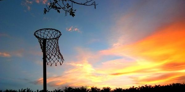 An outdoor netball hoop silhouette set against the sky at dusk