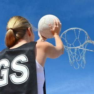Woman shooting a goal in netball